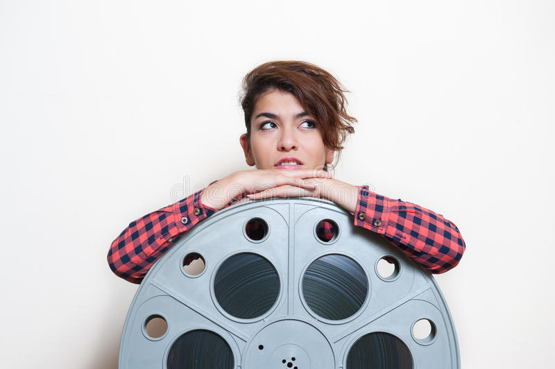 Young woman sitting behind big cinema movie reel stock images