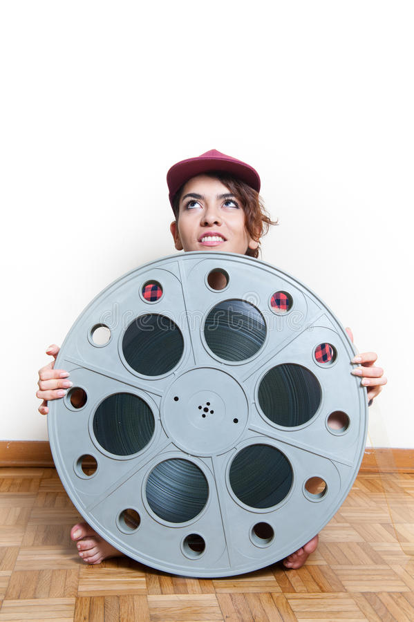 Young woman sitting behind big cinema movie reel royalty free stock image