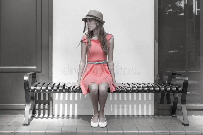 Young woman sitting on bench stock photos