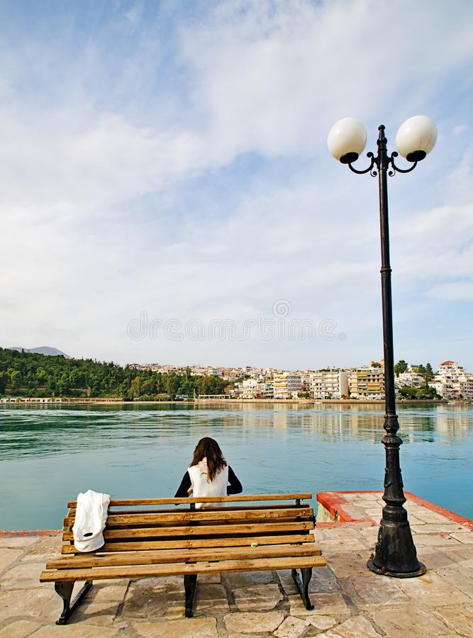 Young woman  sitting on a bench. Young woman sitting on a bench at Chalkida city coast, cloudy winter day stock photography
