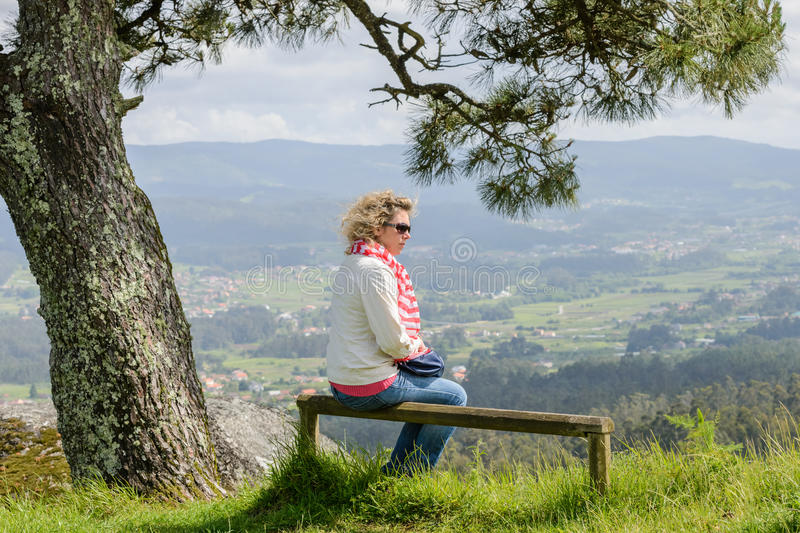 Young woman sitting on a bench looking at the nature stock photography