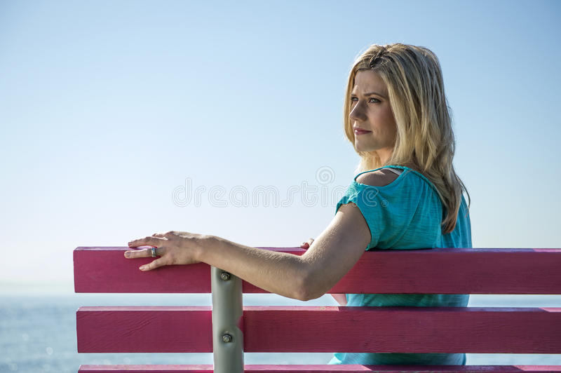 Young Woman Sitting on a Bench, at the sea side royalty free stock photography
