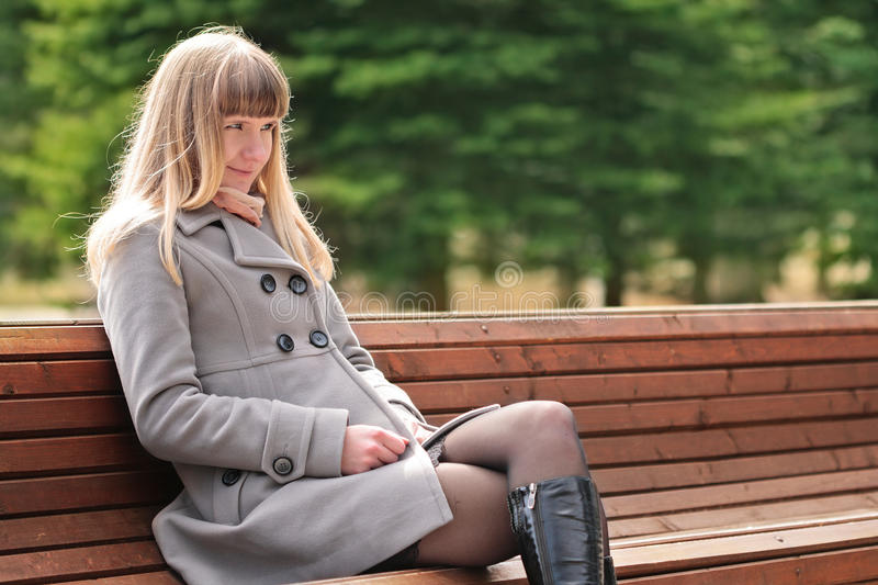 Young woman sitting on bench stock photo