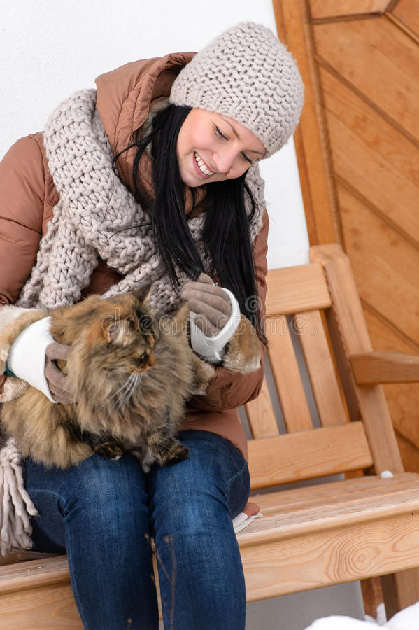 Young woman sitting bench winter stroking cat. Young woman sitting on bench outside winter cottage stroking cat stock images