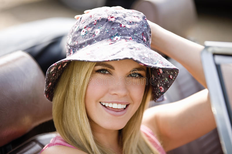 A young woman sitting in a black sports car wearing a summer hat, close up stock image