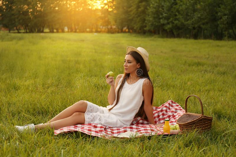 Young woman sitting on  blanket in park. Young woman sitting on picnic blanket in park stock image