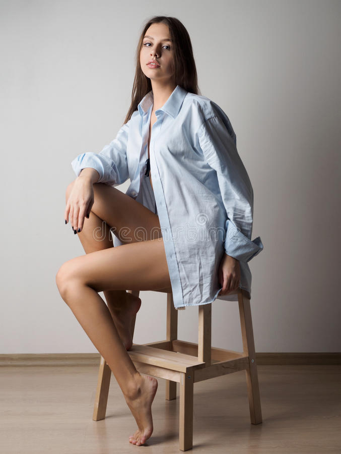 Young woman sitting in blue mens shirt royalty free stock photos