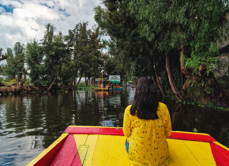 Young woman sitting on boat navigates on Xochimilco canal royalty free stock image