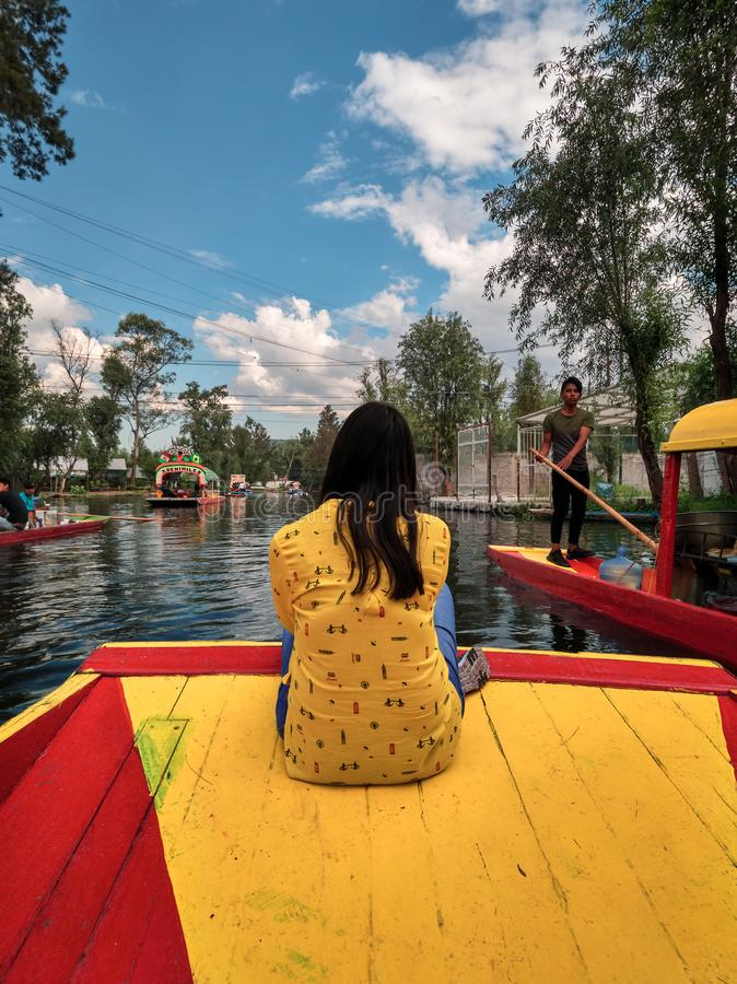 Young woman sitting on bow of traditional Xochimilco boat stock photo