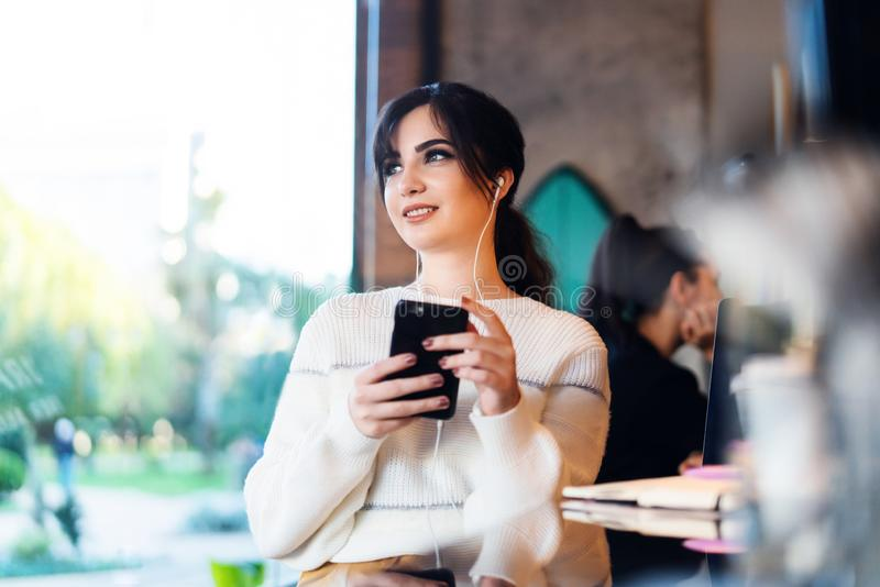 Young woman sitting cafe at table, thoughtfully looking out window, holding smartphone.Portrait girl with cell phone in her hands stock photography