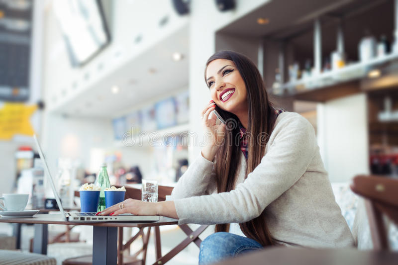 Young woman sitting in the cafeteria with laptop and using mobile phone royalty free stock photos