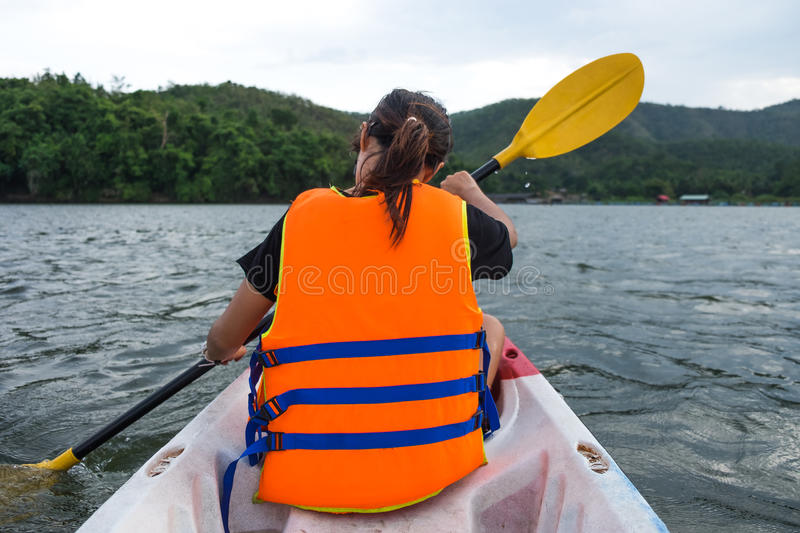 Young woman sitting on canoe boat and rowing in lake stock photography