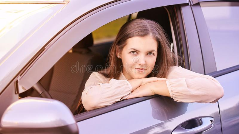 Young woman sitting in car. Ride instruction. Automobile loan.  stock photography