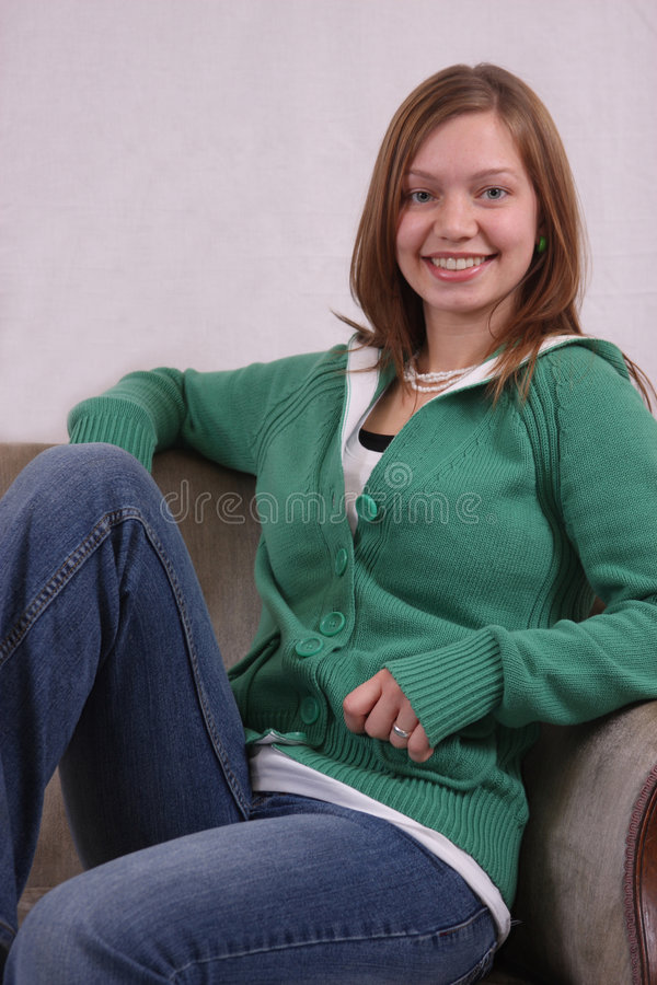 Young woman sitting in a chair. A smiling young woman posed sitting in a chair royalty free stock images