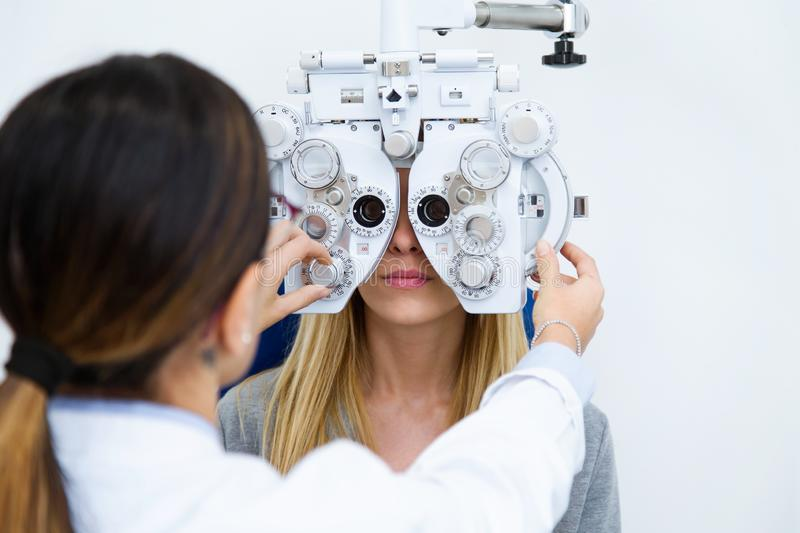 Young woman sitting on chair with beautiful optician standing while doing eye test in ophthalmology clinic royalty free stock photography