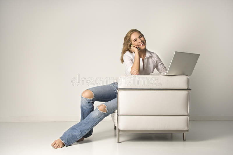 Young Woman Sitting on Chair with a Laptop and Cel stock photo