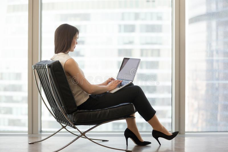 Young woman sitting in chair using laptop for studying online royalty free stock photography