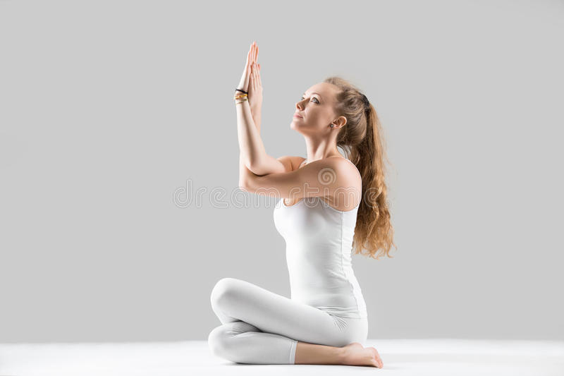 Young woman sitting in Cow Face pose, grey studio background stock photos