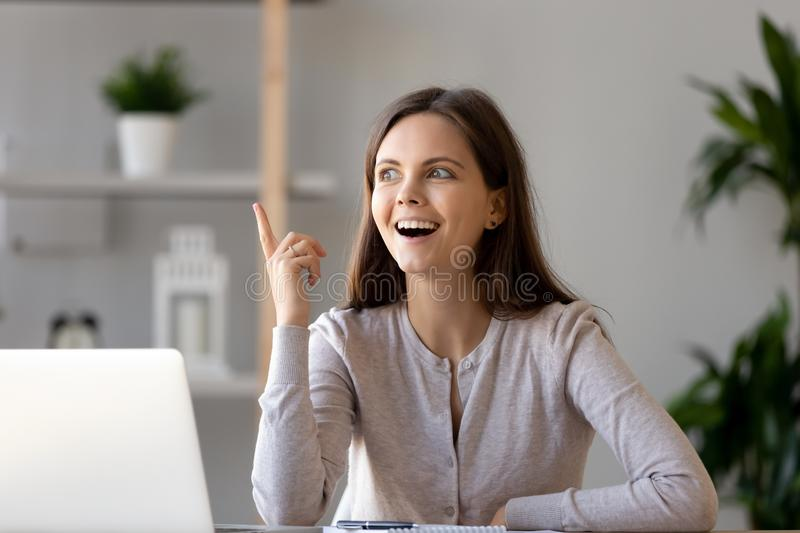 Young woman sitting at desk feels excited with good idea royalty free stock photography