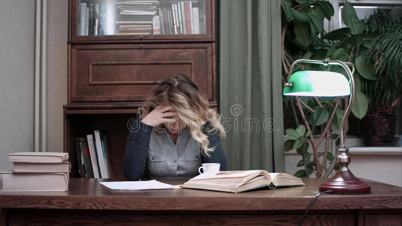 Young woman sitting at desk tired of working and taking her head in hands stock photo