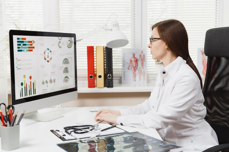 Young woman sitting at desk, working on modern computer with medical documents in light office in hospital. Female stock image