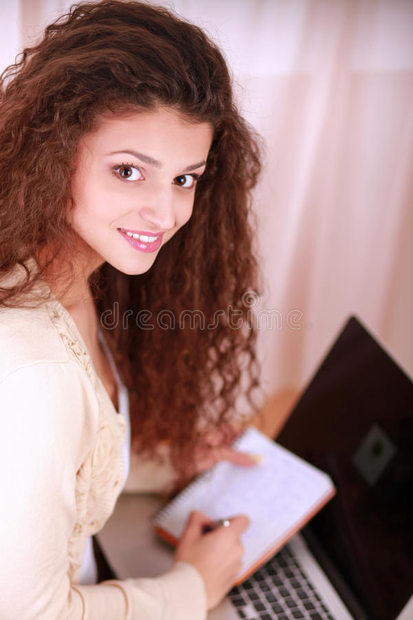 Young woman sitting down smiling holding laptop.  stock images