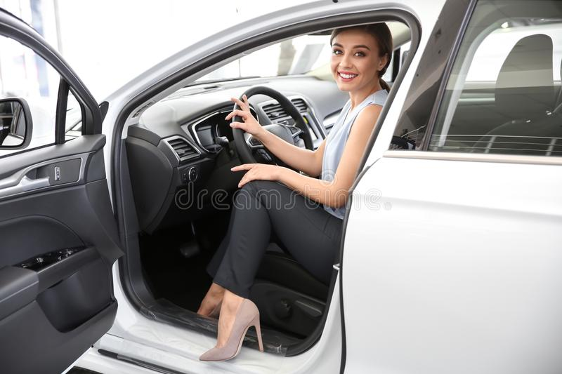 Young woman sitting in driver`s seat of new car. At salon royalty free stock photo