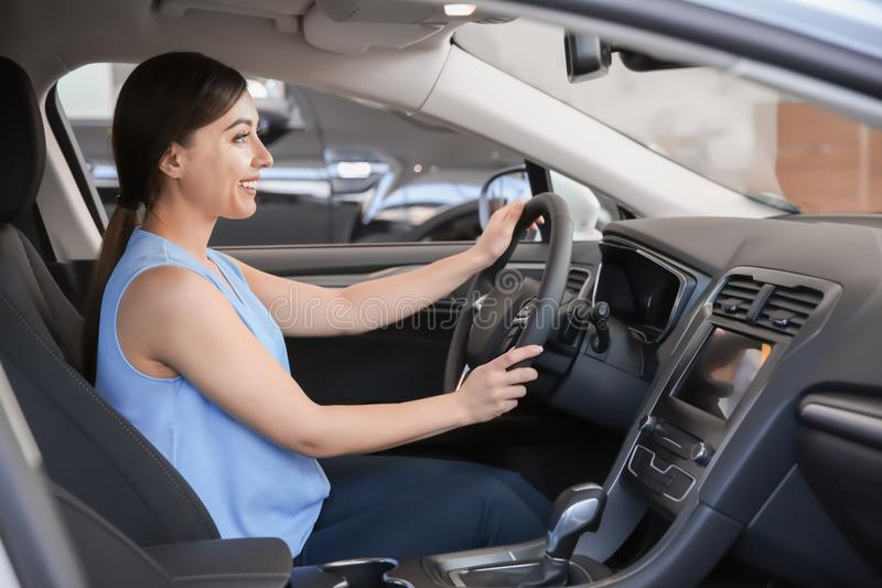 Young woman sitting in driver`s seat of new car. At salon stock photography
