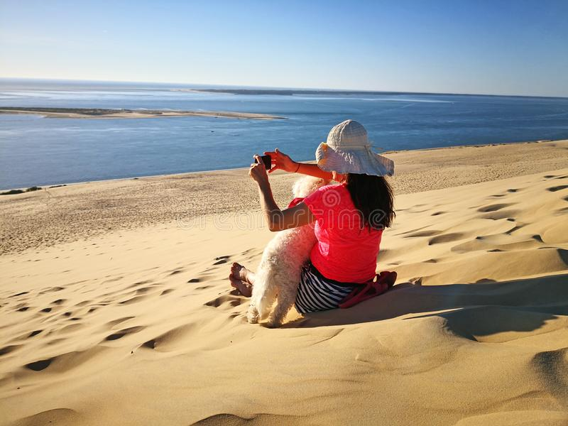 Young woman sitting on a dune photographing with smart phone beautiful landscape stock image