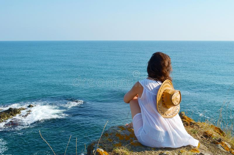 Young Woman Sitting on the Edge of a Rocks above the Sea stock photo