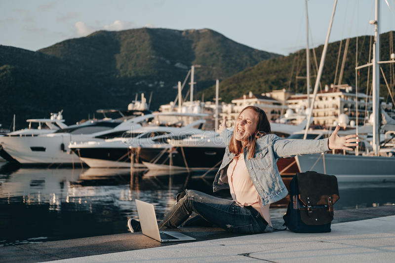 Young woman sitting on Embankment on the beach at sunset and prints in the laptop. Vacations, freelancer, lifestyle, Successful c royalty free stock images