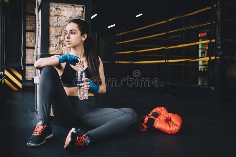 Young woman sitting on the floor after hard workout in gym. royalty free stock photo