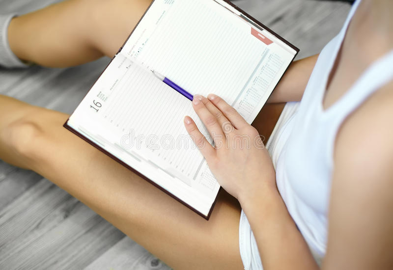 young woman sitting on floor and making notes to her diary stock image
