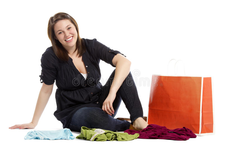 Young woman sitting on the floor with new clothes stock photos