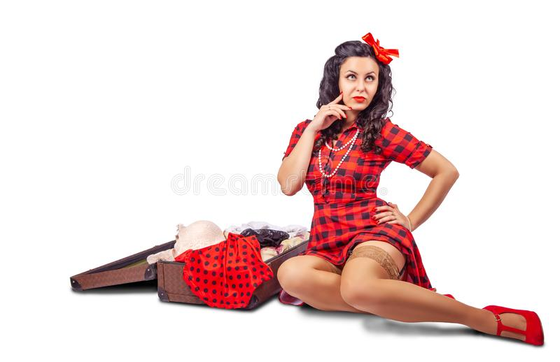 Young woman sitting on the floor and putting clothes in a suitcase stock photography