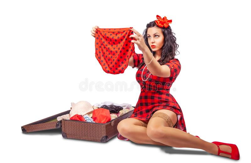 Young woman sitting on the floor and putting clothes in a suitcase royalty free stock photos