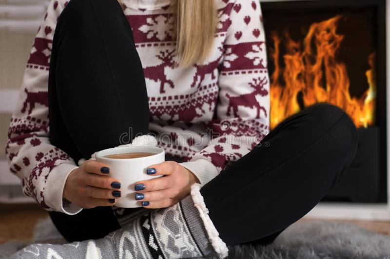 Young woman sitting in front of the fireplace at home and warming on fire. Young girl sitting in front of the fireplace at home and warming on fire. Girl hold royalty free stock image