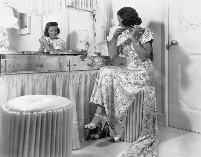 Young woman sitting in front of her vanity doing her hair stock photo