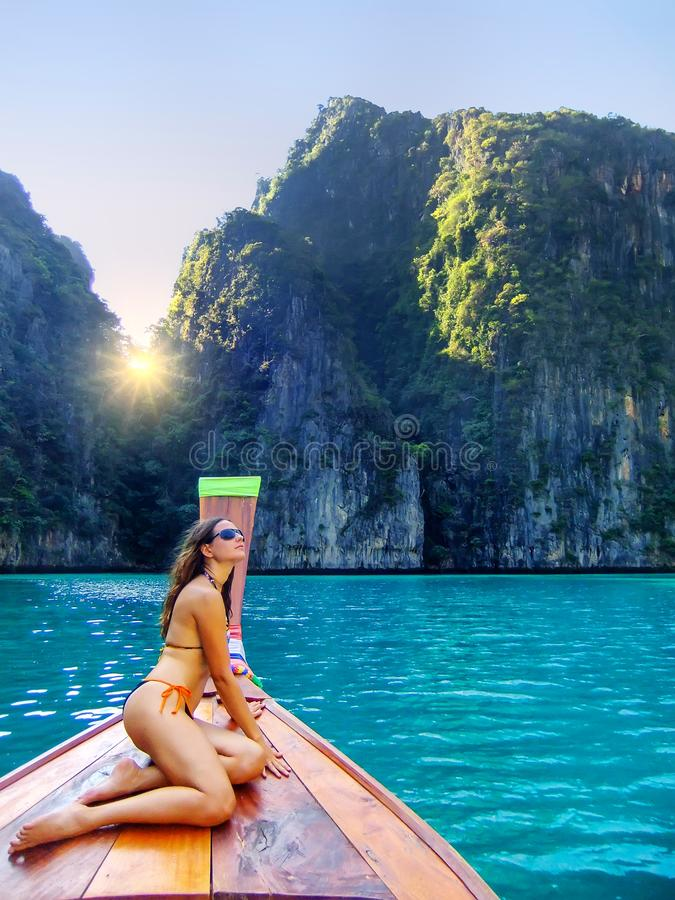 Young woman sitting at the front of longtail boat cruising Phi Phi Leh Island, Krabi Province, Thailand stock images