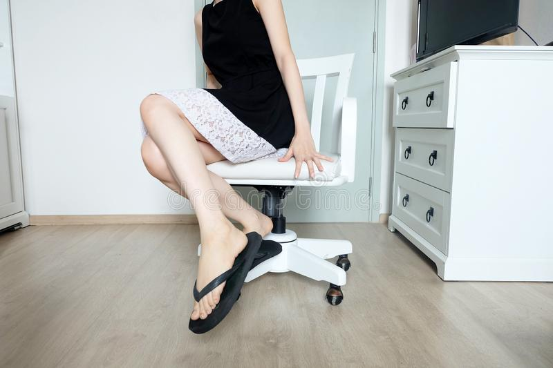 Young Woman Sitting. Girl in Black Dress Sit. Beautiful Female Slim Legs on White Chair with Stylish Black Shoes in the White Room royalty free stock photos