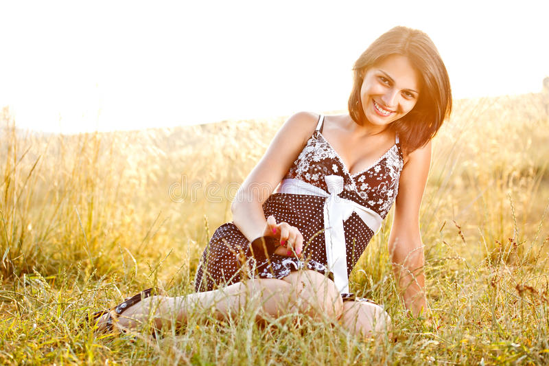Young woman sitting on the grass royalty free stock photo