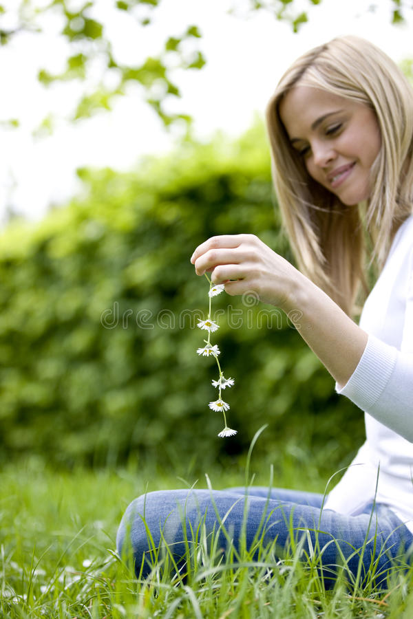 A young woman sitting on the grass, holding a daisy chain royalty free stock photo