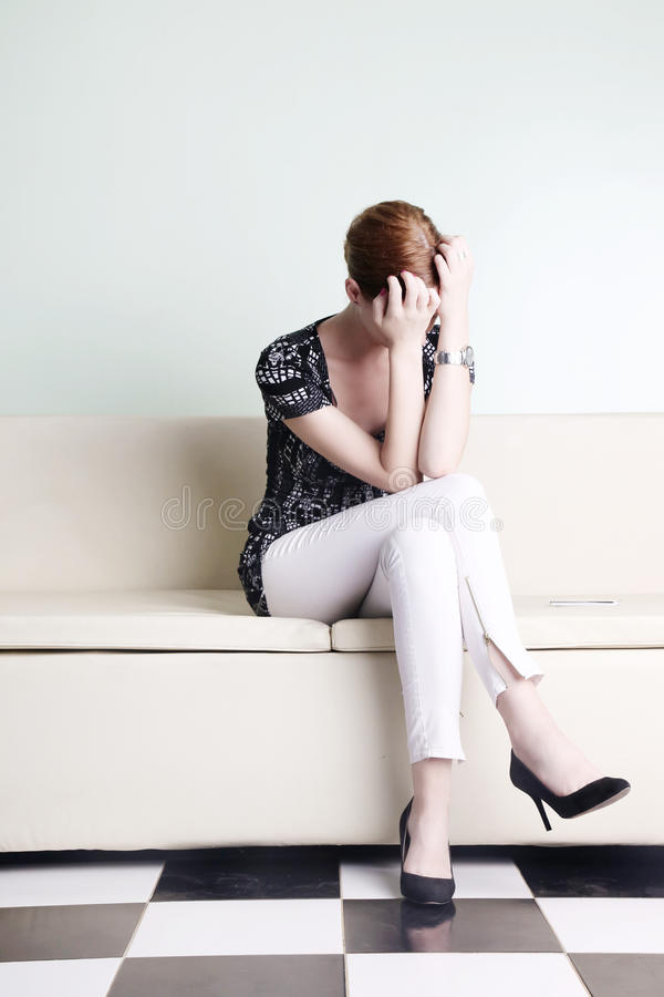 Young woman sitting with hands over her face stock images
