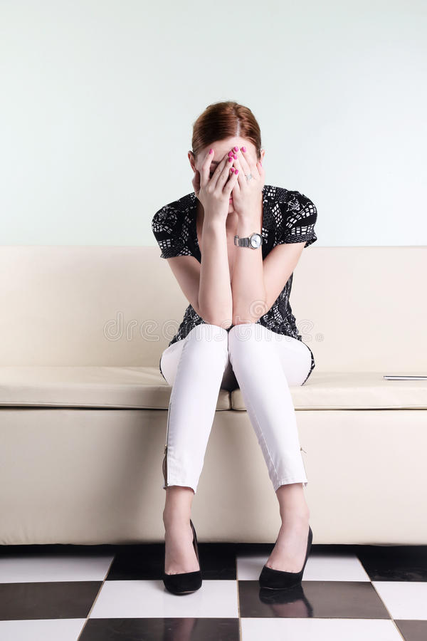 Young woman sitting with hands over her face royalty free stock photo
