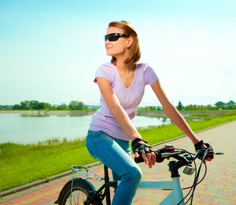 Young woman is sitting on her bicycle. Young happy woman is sitting on her bicycle, outdoor shoot stock photo