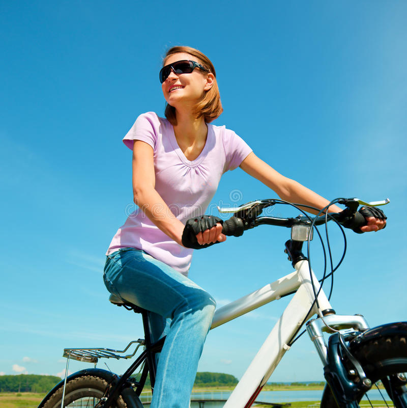 Young woman is sitting on her bicycle. Young happy woman is sitting on her bicycle, outdoor shoot royalty free stock photo