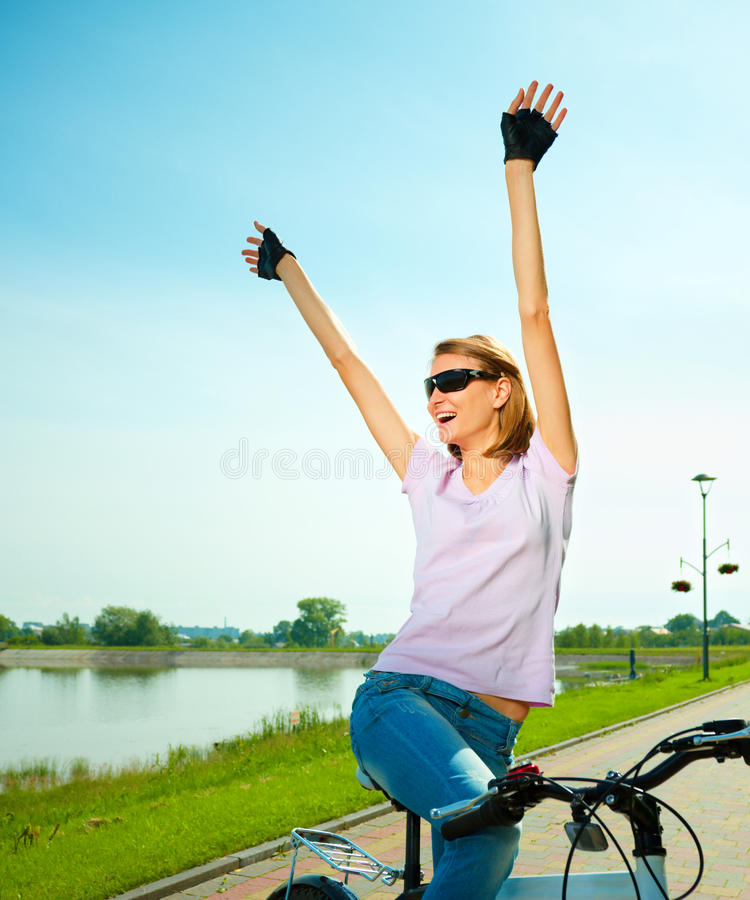 Young woman is sitting on her bicycle. Young happy woman is sitting on her bicycle while raising hands up in joy, outdoor shoot royalty free stock photo