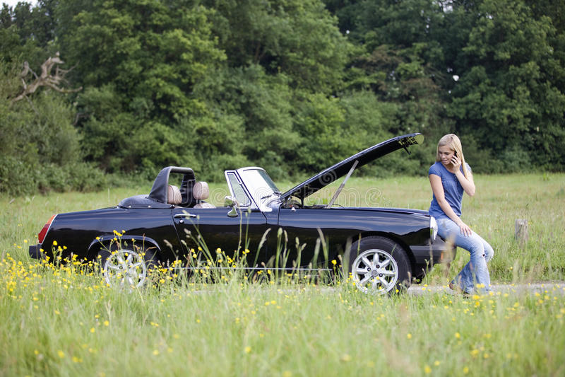 A young woman sitting on her broken down car speaking on a mobile phone royalty free stock photos