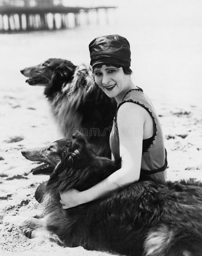 Young woman sitting with her Collies on the beach stock photo
