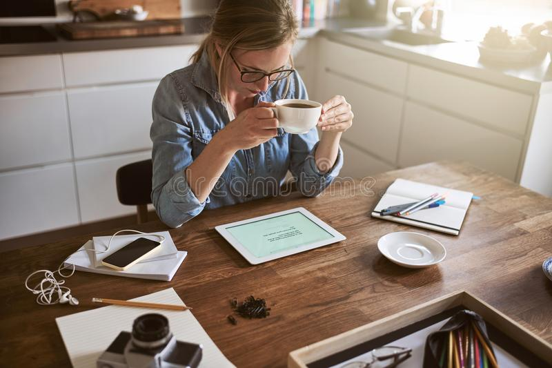 Young woman drinking coffee and working online at home. Young woman sitting at her kitchen table at home drinking a cup of coffee and working on her small stock photos